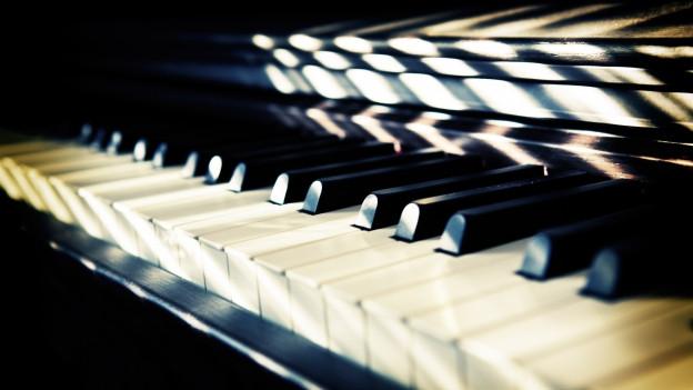 Schatten fallen auf eine Klaviertastatur.