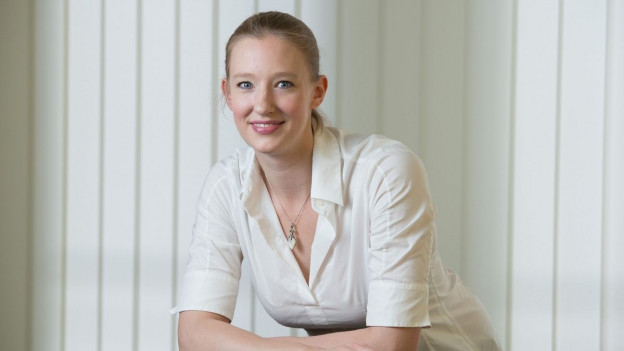Junge Frau mit blonden Haaren und weisser Bluse