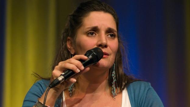 Frau mit langen braunen Haaren spricht in ein Mikrofon