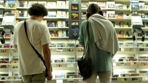 Zwei Männer hören sich im Geschäft CDs an.