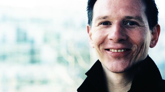 Das Porträt eines Mannes mit kurzen, dunklen Haaren, der in die Kamera lächelt.