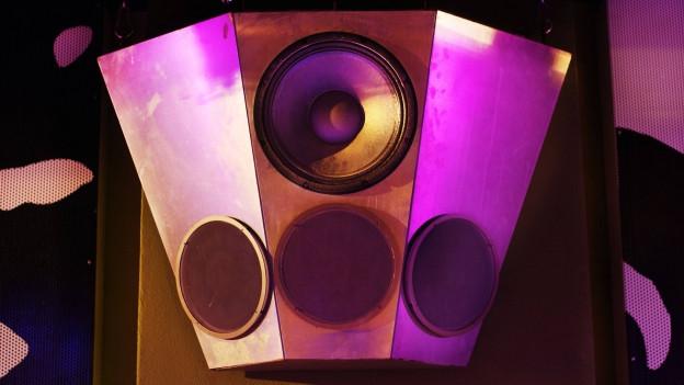Lila-gelb beleuchtete Lautsprecher in einem Club.