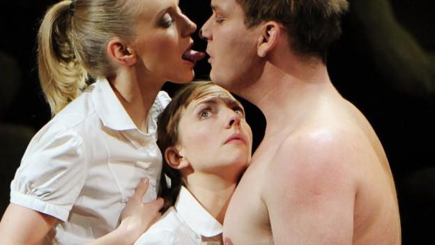 Drei Personen eng umschlungen: Die Äusseren versuchen sich zu küssen.