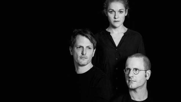 Eine Frau und zwei Männer vor schwarzem Hintergrund.