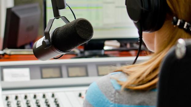 Frau von hinten im Radiostudio vor dem Mikrofon.