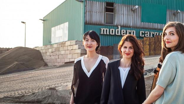 Drei Frauen schauen freundlich in die Kamera. Im Hintergrund ein Industriegebiet mit Sand.
