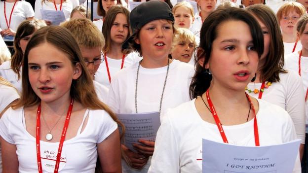 Eine Schulklasse singt, zuvordert zwei Mädchen. Alle tragen weisse Shirts mit einem roten Bändel.