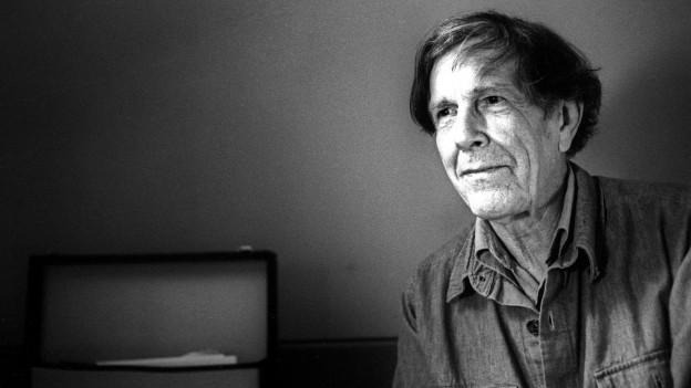 Schwarz-Weiss Fotografie eines älteren Mannes mit halb langen Haaren.