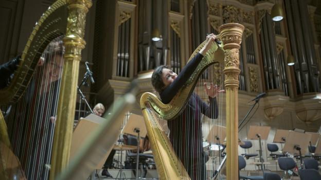 Zwei Harfenistinnen beim Stimmen ihrer Instrumente