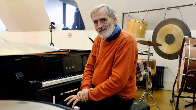 Ein Mann mit Bart umringt von Schlagwerk, Klavier und Pauke.