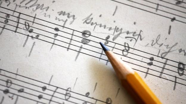 Symbolbild: Notenpapier mit Handschriftlichen einträgen.