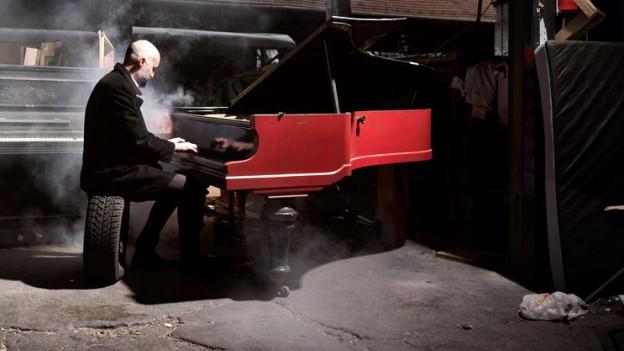 Ein Mann sitzt auf einem Autoreifen und spielt Piano.