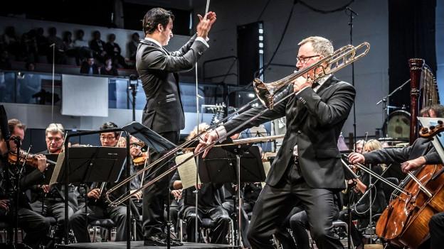 Mike Svoboda spielt Posaune auf einer Bühne, um ihn ein Orchester.