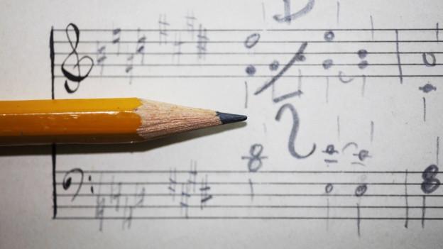 Ein Bleistift liegt auf einem Notenblatt.