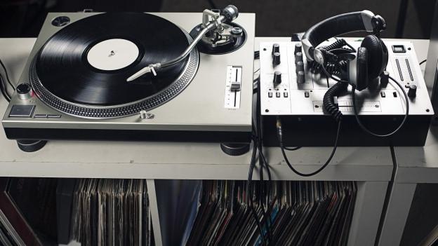 Ein Plattenspieler, Kopfhörer und DJ-Mischpult auf einem Regal mit Schallplatten