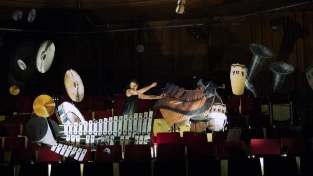 Eine Frau auf einer Publikumstribüne scheint mit Perkussionsinstrumenten um sich zu schmeissen