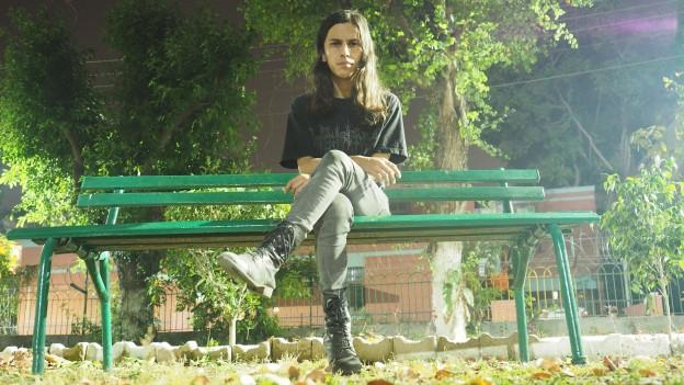 Ein junger Mann mit langen dunklen Haaren sitzt auf einer Parkbank und schaut in die Kamera
