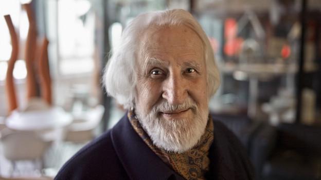Ein alterer Herr mit weissen Haaren, Bart und freundlichem Gesichtsausdruck