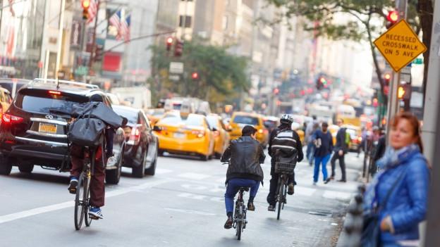 Fahrradfahrer auf einer dichtbefahrenen Strasse einer Grossstadt