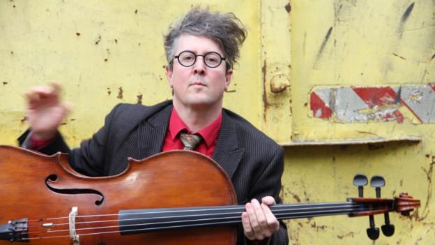 Der Künster mit wilden, grauen Haaren und schwarzer Brille mit seinem Cello