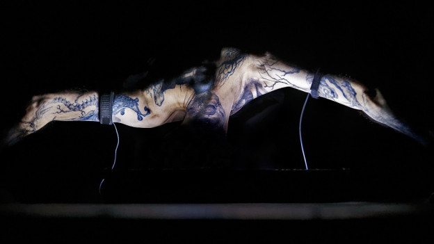 Mann mit Tatoos performt zu Musik