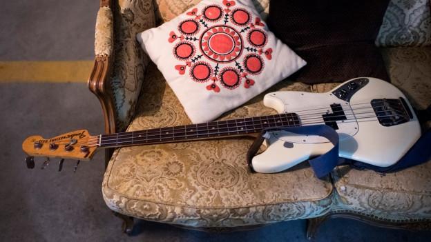 Eine Gitarre liegt auf einem Sofa