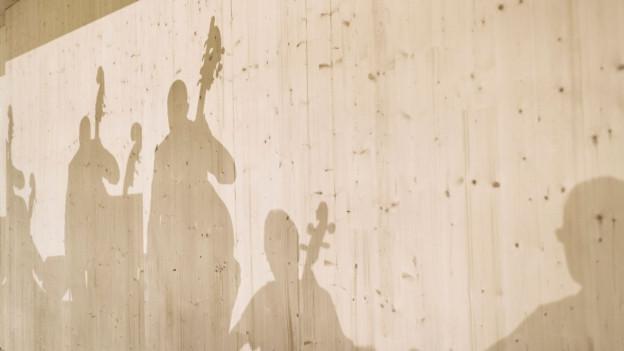 Schatten von Musikern auf einer Holzwand.