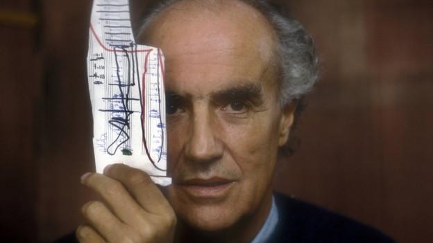 Ein Herr mit kurzen grauen Haaren hält sich einen Fetzen beschmierten Notenpapiers vor die rechte Gesichtshälfte