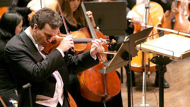 Mann spielt konzentriert Geige.