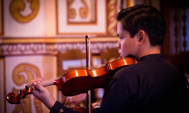 Ein Junge mit Geige in einer Kirche.