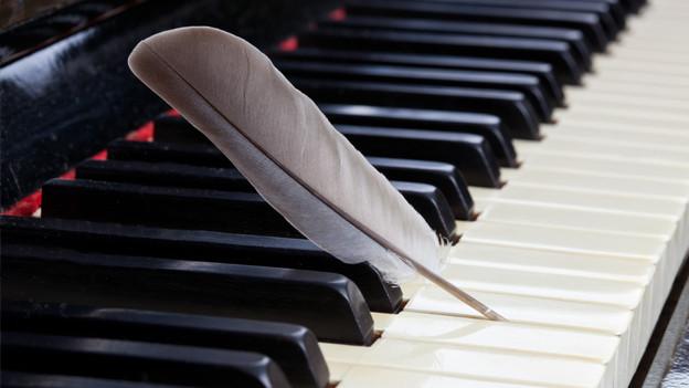 Feder auf Klavier-Partitur.