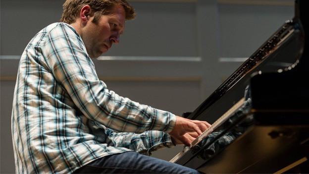 Mann spielt Klavier.