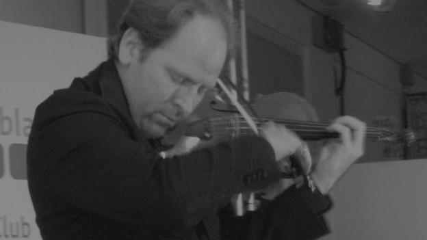Ein Mann spielt Violine. Er trägt einen schwarzen Mantel.