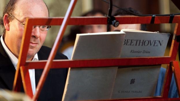 Der Musiker hinter einem Notenständer verborgen, auf dem ein Beethoven-Heft steht.