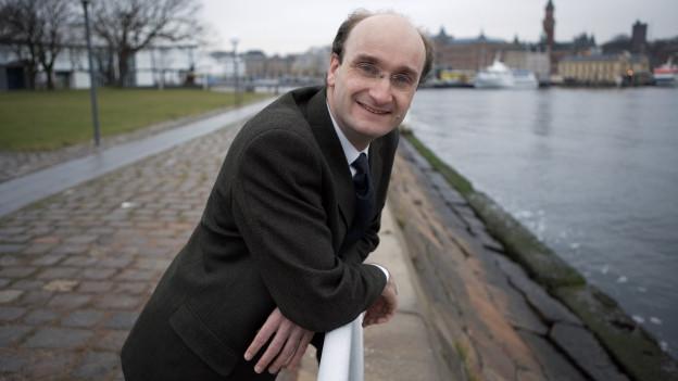 Andrew Manze steht an einem Fluss.