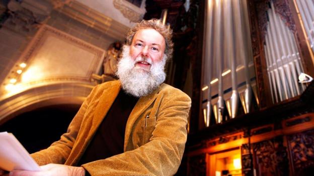 Mann mit Bart vor Kirchenorgel.