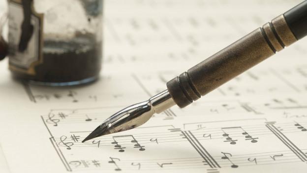 Schreibfeder auf Notenpapier.