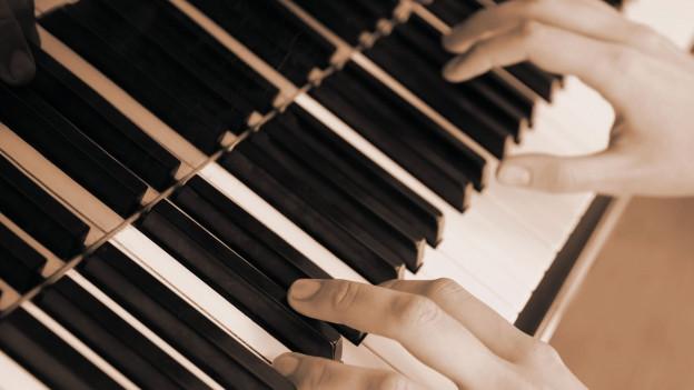 Hände auf einem Klavier