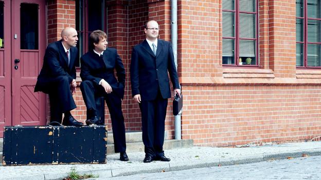 Drei Männer in Anzügen stehen vor einem Backsteingebäude.