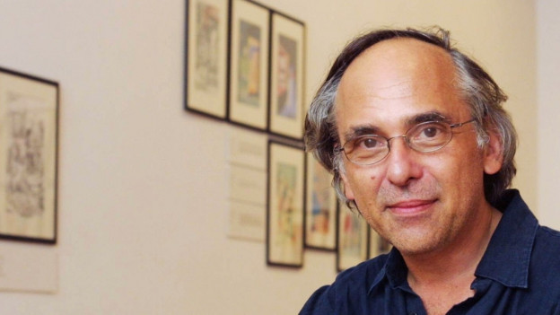 Porträt von Spiegelman in einer Ausstellung, im Hintergrund seine Bilder. Er trägt ein blaues Hemd.