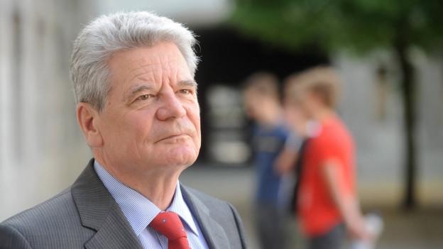 Porträt von Joachim Gauck. Er trägt Anzug mit roter Krawatte, blickt neben die Kamera.