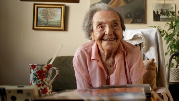 Ein alte Frau sitzt in ihrem Wohnzimmer und lächelt in die Kamera. Im Vordergrund eine Tasse, an der Wand hinter ihr hängen Bilder.