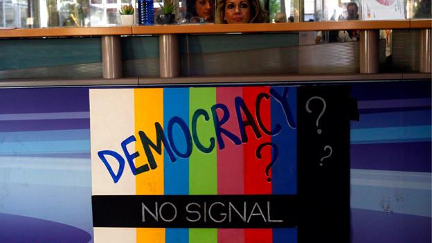 Buntes Schild, auf dem «Democracy? No Signal» steht.