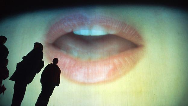 Das Bild eines Mundes ist auf eine Wand projiziert, Menschen gehen daran vorbei