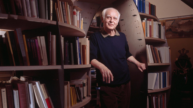 Adolf Muschg steht vor einem Bücherregal.