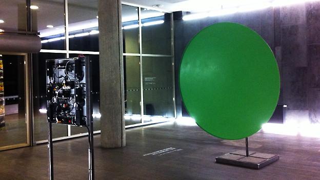 Kunstinstallation: Eine grosse grüne Scheibe steht einem Fernseher gegenüber