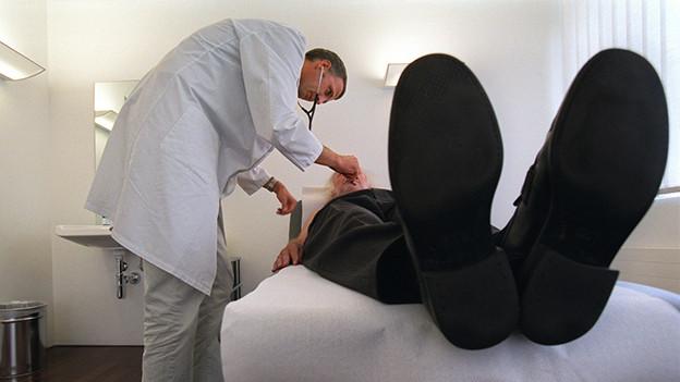 Ein Mann liegt auf einer Liege und wird von einem Arzt untersucht.