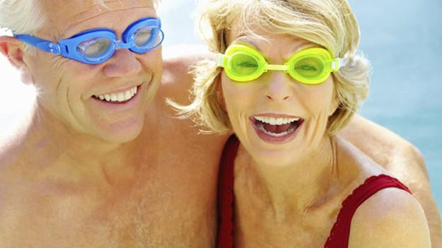 Zwei ältere Menschen mit knallig-farbiger Schwimmbrille.