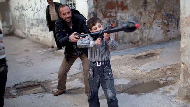 Ein Mann im syrischen Idlib erklärt dem 11-Jährigen Bilal, wie man eine Spielzeug-Panzerabwehrrakete bedient.
