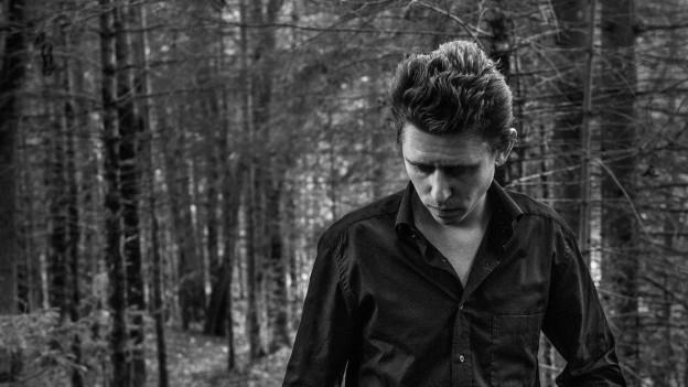 Porträtaufnahme eines Mannes in schwarz-weiss, in einem Wald aufgenommen.